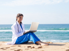 pretty indian intern using laptop on beach